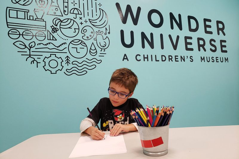 A young boy draws with colored pencils in front of a blue wall with the logo for Wonder Universe.