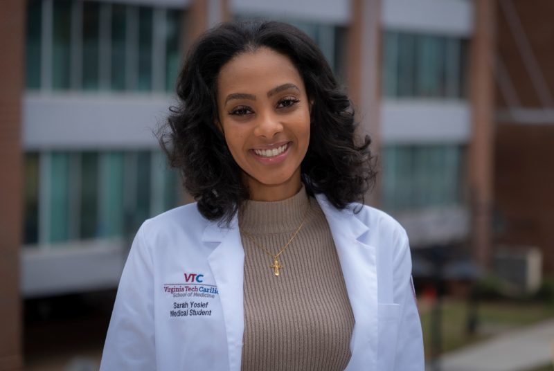 Female wearing medical white coat outside with building in background