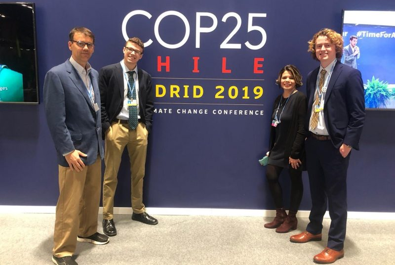 Three men and one woman standing in front of a large wall hanging for COP25.