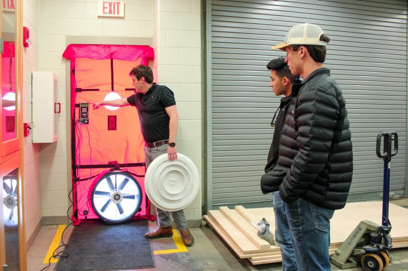 Assistant professor Philip Agee explains how a blower door measures airflow to students in the Myers-Lawson School of Construction