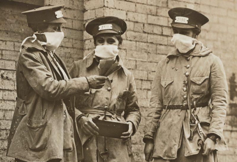 Women conductors in 1918 New York stand nearby on a city street and wear face masks to prevent the spread of influenza during the 1918 flu pandemic. National Archives