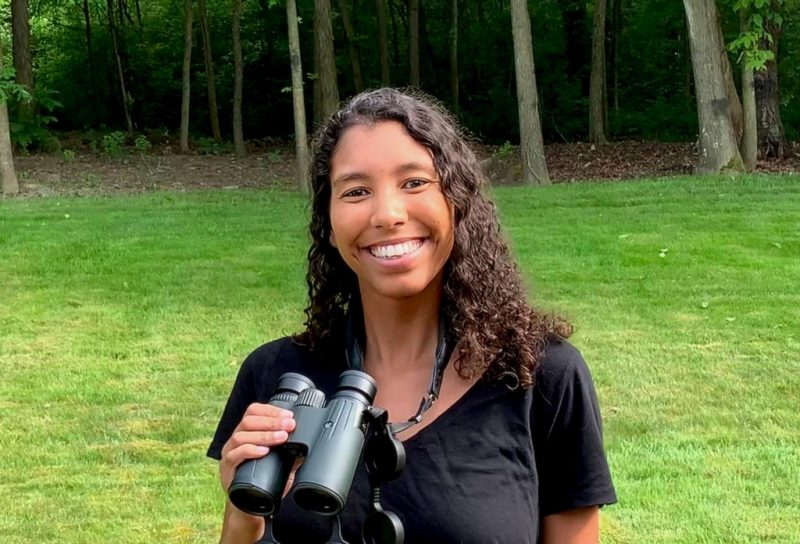 Amber Wendler, a Ph.D. student of Biological Sciences in the College of Science and one of the co-organizers of #BlackBirdersWeek, is smiling while she holds a set of binoculars.