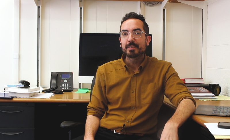Department of Physics Assistant Professor Ian Shoemaker poses for as photograph in his office