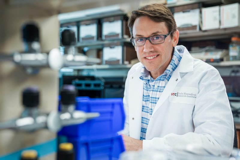 Michael A. Fox poses for a photograph in his lab, wearing a lab coat