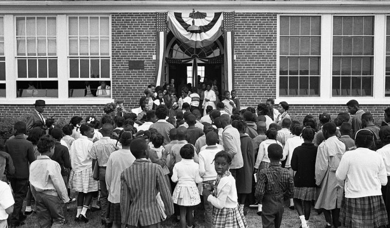 "Dozens of young black children enter the double doors of a school. One black man in a hat and several black women in glasses enter with them. The front door is decorated with American flags and streamers. Two people watch the crowd from inside through the windows. ""African American school children entering the Mary E. Branch School at S. Main Street and Griffin Boulevard, Farmville, Prince Edward County, Virginia."" O'Halloran, Thomas J, photographer. African American school children entering the Mary E. Branch School at S. Main Street and Griffin Boulevard, Farmville, Prince Edward County, Virginia. Farmville Virginia, 1963. Sept. 16. Photograph. https://www.loc.gov/item/2011648793/. No known restrictions on publication."