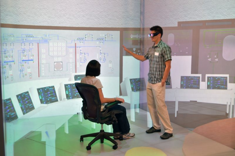 Two nuclear engineering students using a virtual reality system (VRS-RAPID) to view a spent fuel pool at a nuclear power plant.