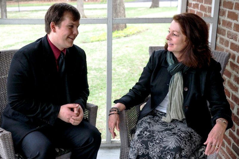 Chris Grogg and Pamela Teaster have a conversation while sitting on a porch