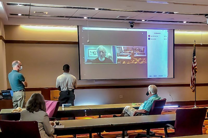Four people, wearing masks and physically distanced at long tables, look up at a large screen where another person joins the meeting via videoconferencing.