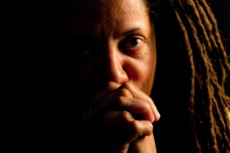 A close up portrait of Nikky Finney with her hands folded in front of her face, looking into the camera.