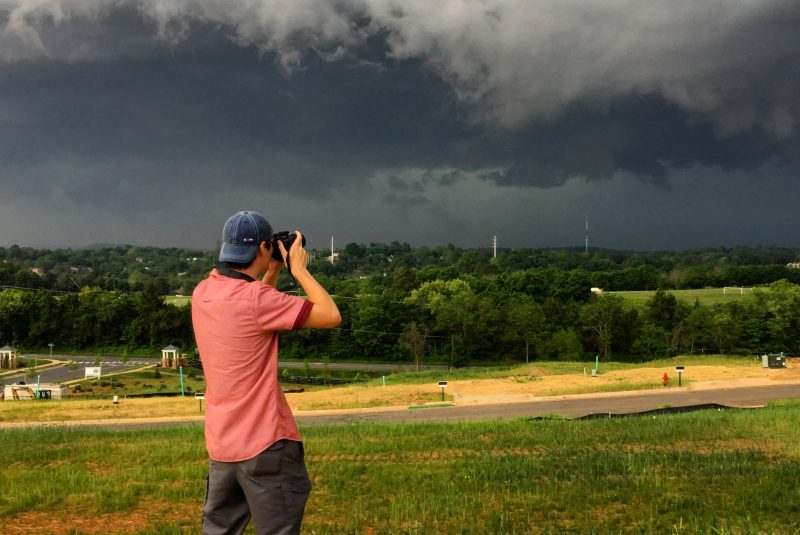 A man with his back to the camera holds a camera, looking towards dark clouds in the distance.
