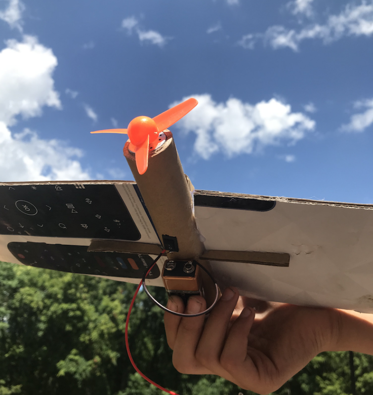 A photo of an airplane made out of cardboard, orange plastic propeller, and battery.
