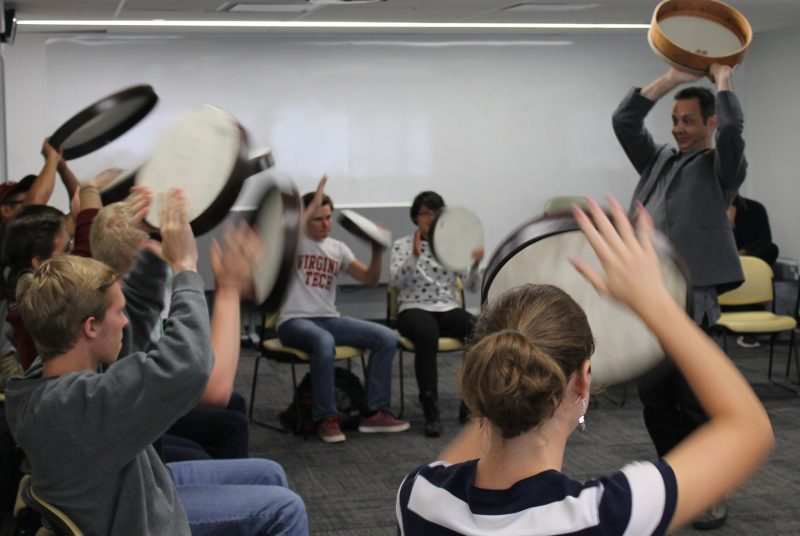 Artist Karim Nagi and a group of Virginia Tech students hold their drums over their heads during a workshop.