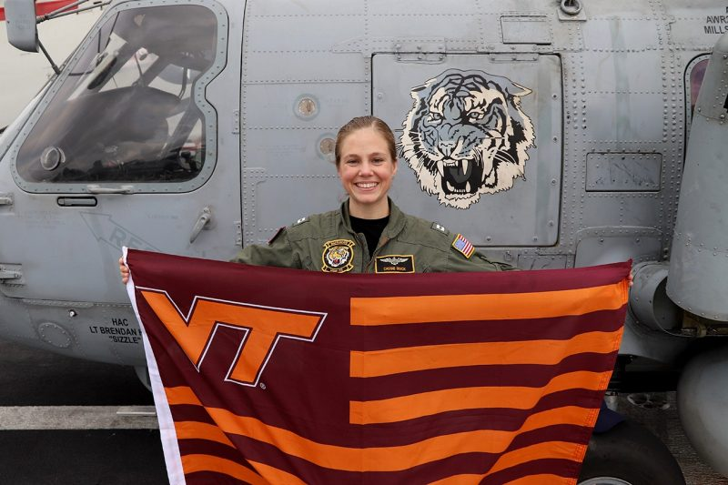 Lt. Cassandra Quick holds a Virginia Tech flag in front of a MH-60 Romeo.