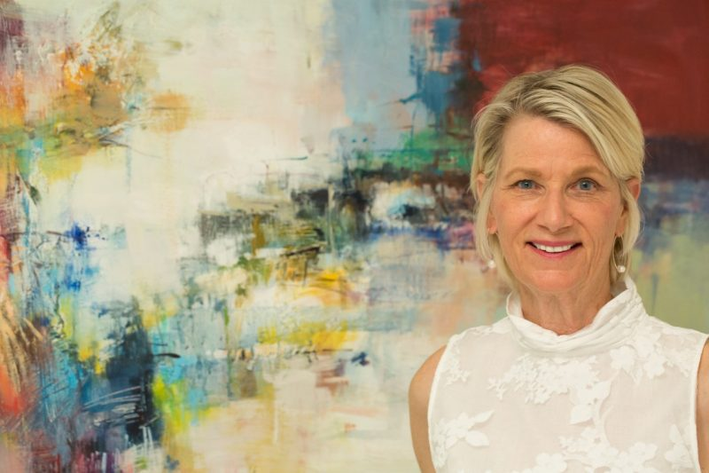 Kay Winzenried stands in front of an abstract painting