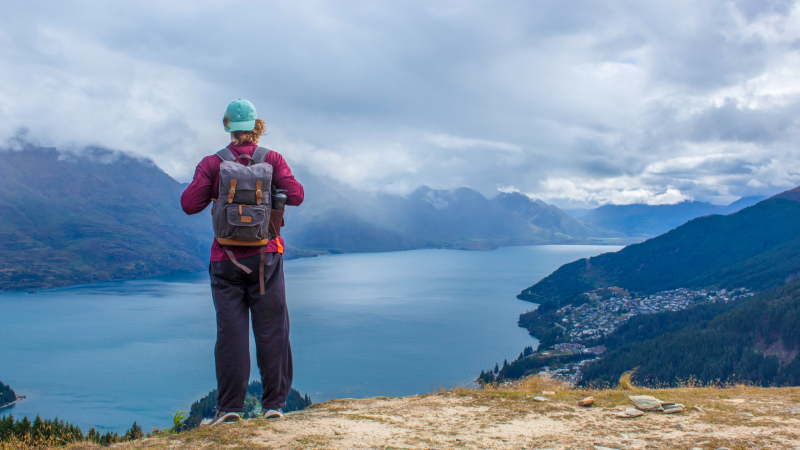 Student on a mountain top overlooks Queenstown, New Zealand.