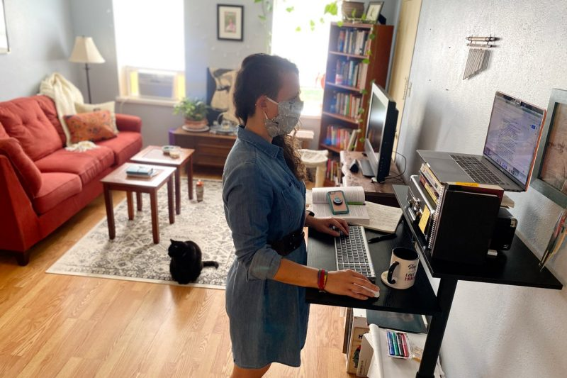 Whitney Hayes stands at her home office desk, while her black cat joins her.