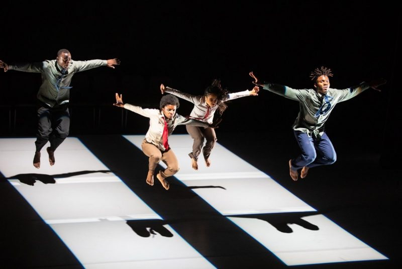 Four barefoot dancers dressed in pants, shirts, and ties are in the air-midjump, arms raised, with their shadows below.