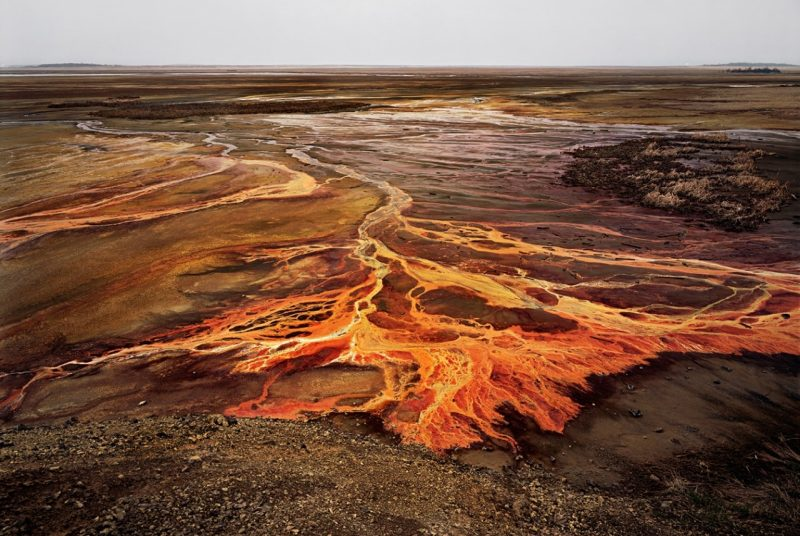 A photograph shows bright orange rivers of nickel tallings, the byproduct of metal extraction.