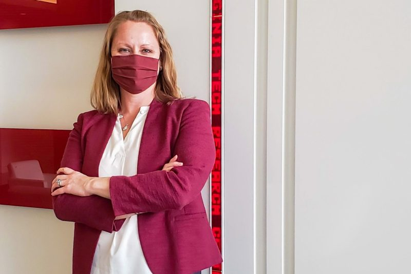 A blonde woman in a maroon mask and business coat stands in front of a white wall.