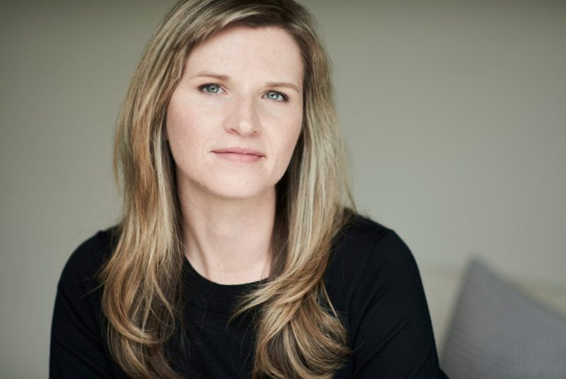 Author Tara Westover poses in a black sweater in front of an off-white background.