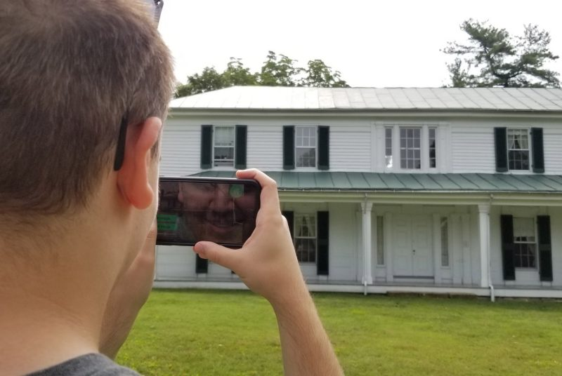 A student holds up a mobile phone and points it toward Solitude, Virginia Tech's oldest building - it's white with black shutters with a big front porch.