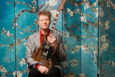Nels Cline, dressed in a suit with a red shirt, sits holding a guitar in his lap in front of an Asian-inspired backdrop with blooming tree limbs.