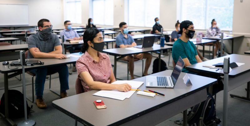 MBA students, all wearing masks, attend a class at the Northern Virginia Center taught by management associate professor Bill Becker (not in photo). Becker's course was offered in a hybrid format (mix of in-person and online classes). The new fully online MBA seeks to offer the best possible educational experience for students who value consistent interaction with their classmates and also want the flexibility of an online format. Photo by Erin Williams