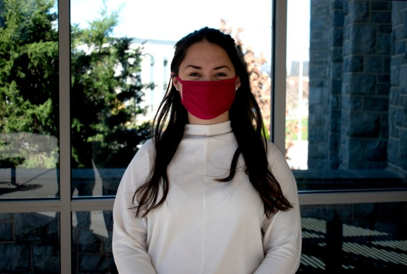 Christine Faunce, wearing a face mask per COVID protection guidelines, stands in front of the Life Sciences 1 building.