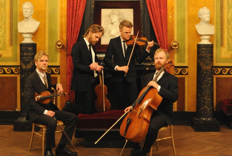 Musicians for the Danish String Quartet pose in an art gallery holding their instruments. Each member is wearing a suit and tie, two are sitting and two are standing in front of a painting and two sculptures.