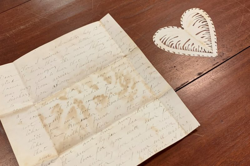 A hand written letter by Virginia Cross and a delicately cut paper heart.