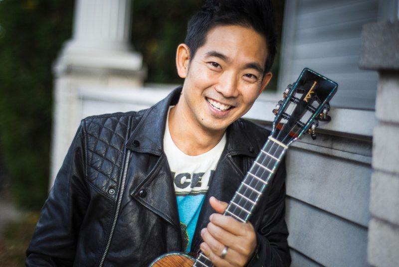 Musician Jake Shimabukuro poses in front of a house in a black leather jacket holding a ukulele.