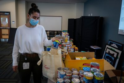 Luma Abunimer walks around room to fill up bag with donations