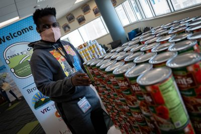 A medical student helps load up a donation bag with canned food
