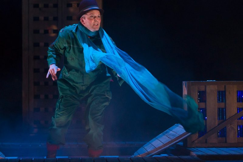 "Performer Louis Lovett wears a hat and flowy scarf as he navigates boxes onstage for the production ""The Girl Who Forgot to Sing Badly."""