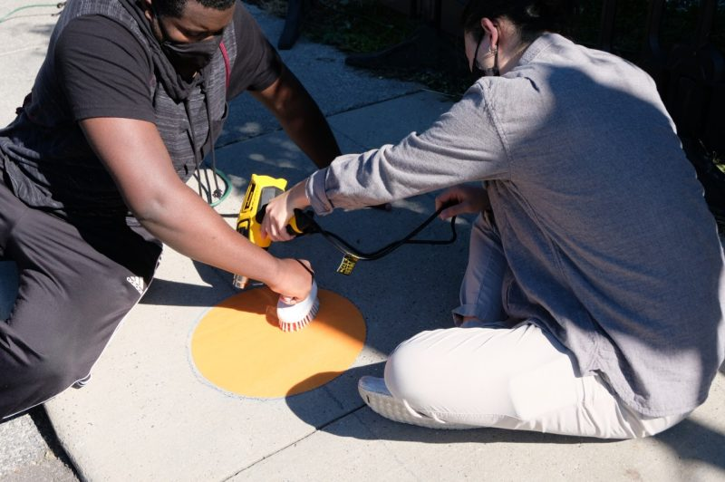 Students install orange circles, as part of the Hokie Circles project, on Blacksburg sidewalks to encourage physical distancing. Photo courtesy of Aki Ishida.