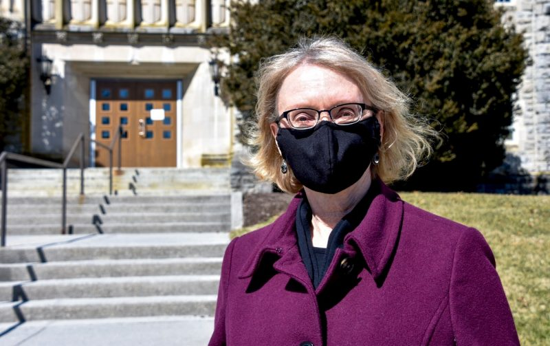 Martha Ann Bell, a newly appointed University Distinguished Professor in the  Department of Psychology, poses wearing a COVID mask in front of Williams Hall. Photo by Melissa Vergara.