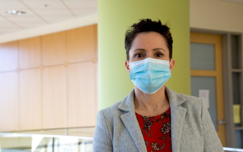 Michelle Olsen, wearing a COVID mask, red blouse, and gray blazer, poses for a photograph inside the Life Sciences 1 building on campus.
