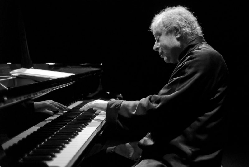 This black and white photo shows Andras Schiff at the piano getting ready to touch the keys with his left hand.