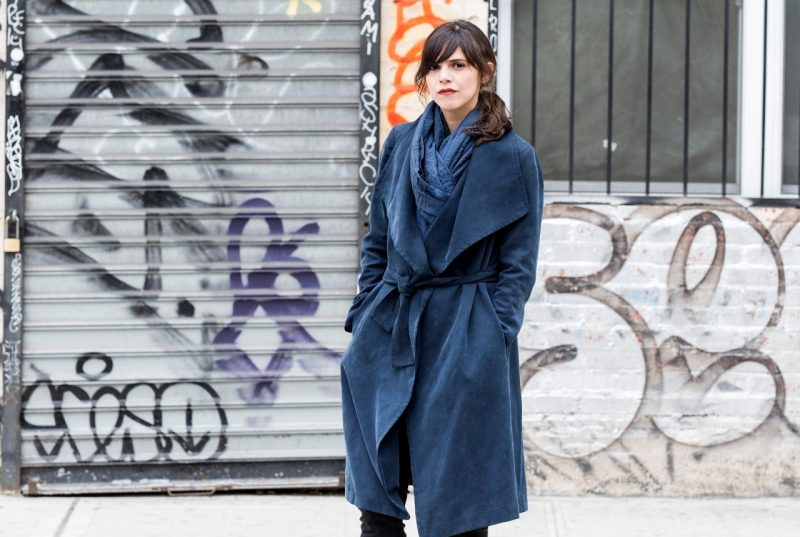 Author Valeria Luiselli stands outside in front of an industrial-looking wall covered in street art with a dark blue sashed overcoat and matching scarf.