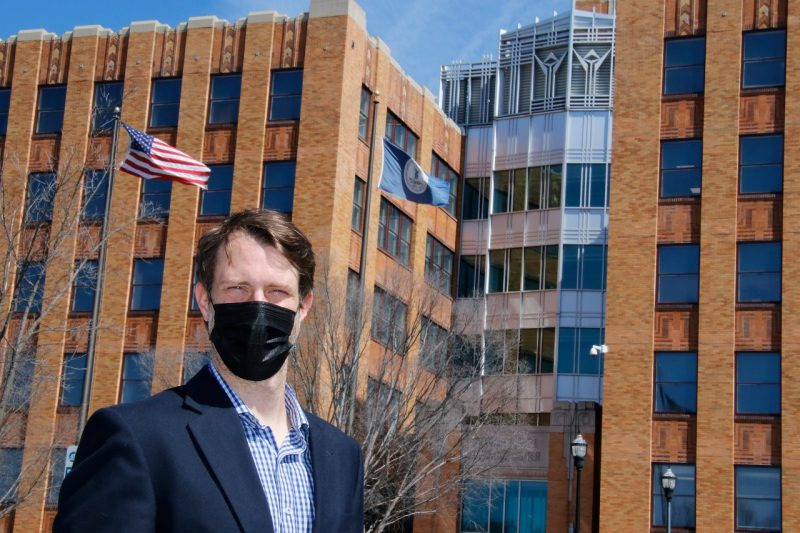 David Conners, wearing a black face mask, stands in front a tall brick building.