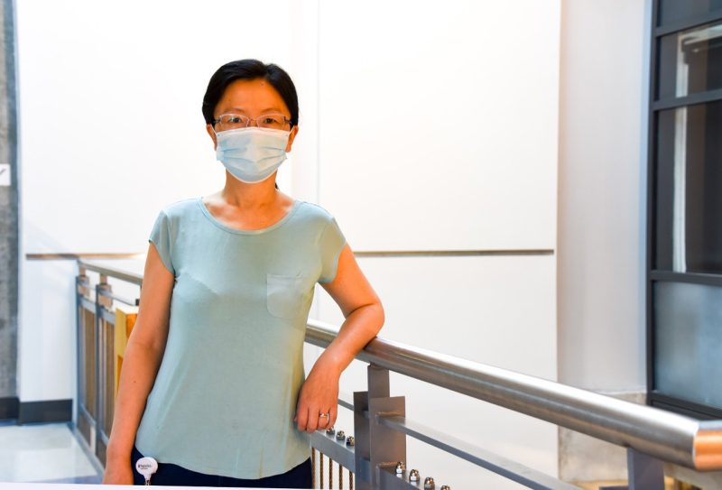 Lini Ni, an assistant professor of neuroscience, poses for a photo in a research building on the Virginia Tech campus. She is wearing a light blue shirt and COVID-standard mask.