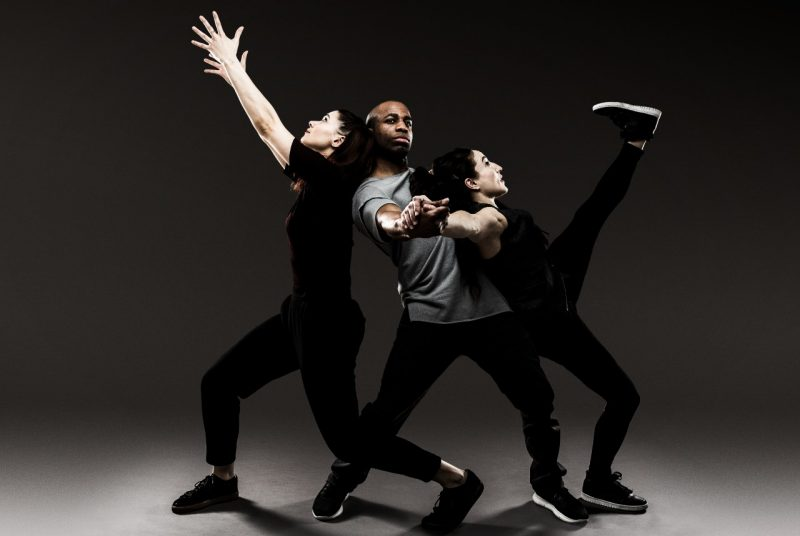 Three dancers all dressed in dark colors pose closely together - one reaching for the sky while the one in the middle holds up the other - in front of a gray background.
