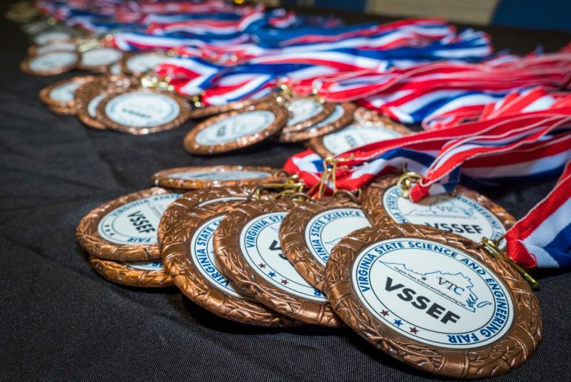 Red, white, and blue award medals draped across a table