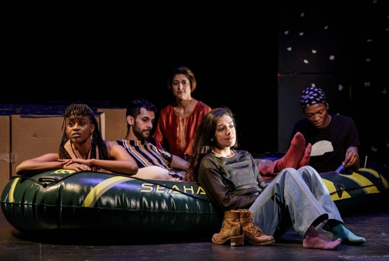 "Five young people, members of the cast of the multimedia play ""Cartography,"" sit in an inflatable raft onstage in front of a group of cardboard boxes."