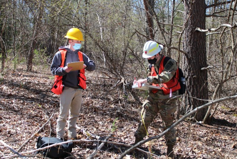 Two young men wearing hard hats, reflective vests, and face coverings and holding clipboards take notes in a wooded area.