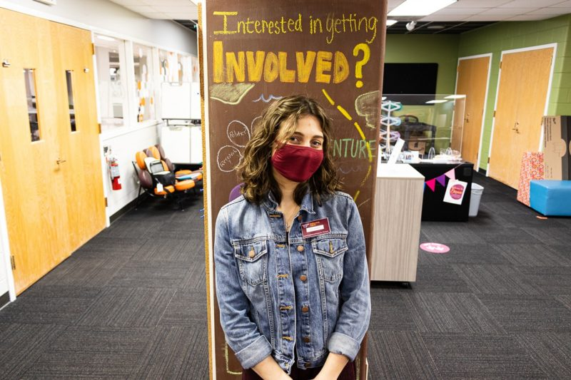 "Delaney Tifft stand in front of a sign that reads ""Interested in getting involved?"""