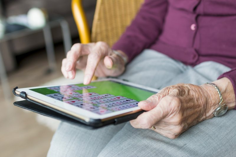 An elderly woman plays solitaire on her tablet.