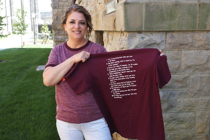 Tammy Henderson holds up a maroon t-shirt with white lettering