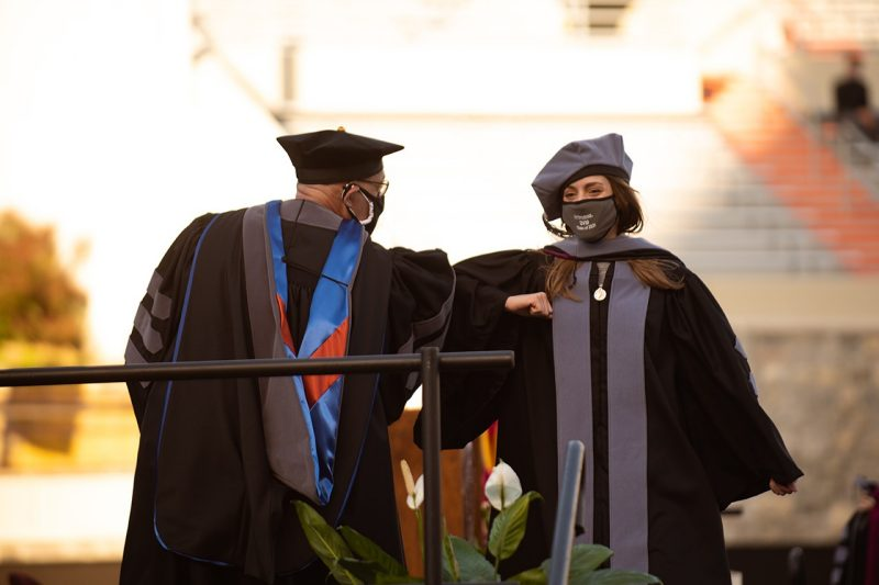 A newly hooded veterinary college graduate bumps elbows to celebrate