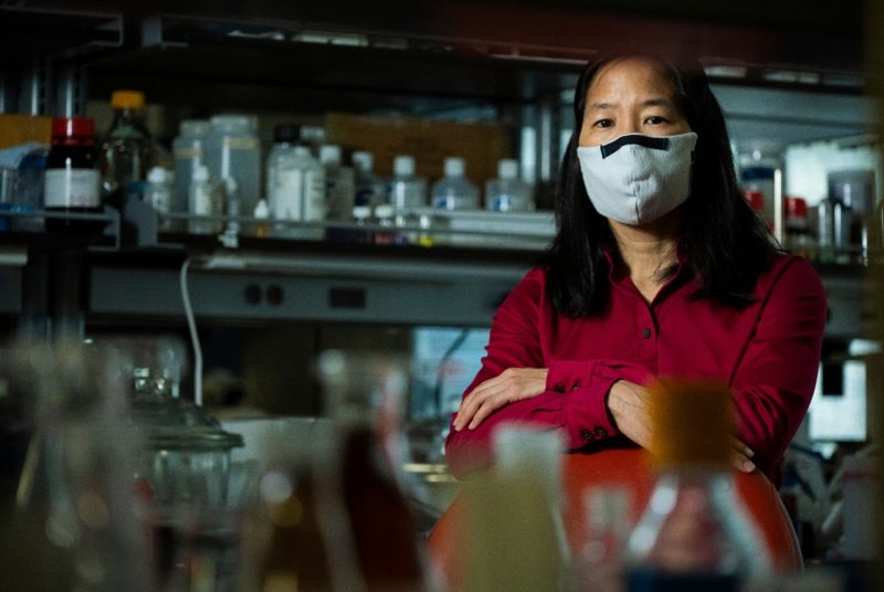 Woman wearing red shirt and mask sitting in scientific laboratory